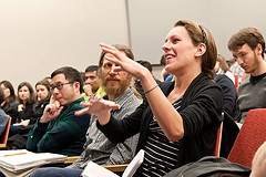 Young woman gesturing among a crowd of students in an STVP entrepreneurship course